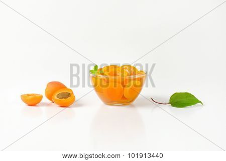 side view of compote apricots, served in the glass bowl