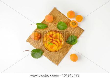 overhead view of compote apricots in the glass bowl with straw linen