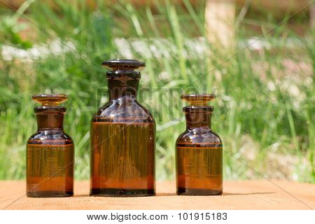 little brown bottles on booden board and green grass