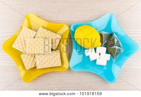 Plates With Lemon, Sugar, Tea Bags And Wafers On Table