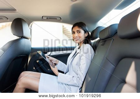 beautiful businesswoman with tablet computer in a car