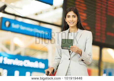 business traveller holding passport and boarding pass in front of flight information board at airport