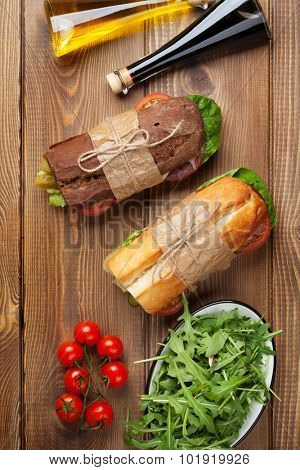 Two sandwiches with salad, ham, cheese and tomatoes, salad and spices on wooden table. Top view