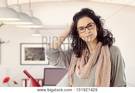 Portrait of casual mid adult caucasian businesswoman at home. Hand in hair, wearing glasses, looking at camera, standing, scarf around neck.