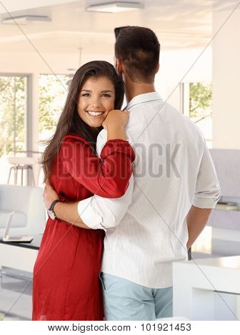 Attractive young caucasian brunette woman at home in the arms of boyfriend. Smiling, looking at camera, hugging, cuddling.