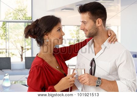 Happy romantic young casual caucasian couple with champagne at home. Attractive woman and handsome man clinking glasses. Smiling standing, embracing, eye contact.