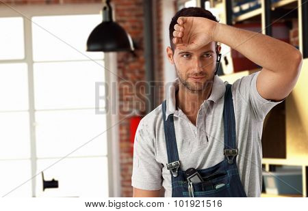 Handsome casual tired bristly caucasian handyman at workshop. Standing in workwear, wearing wireless headset hand wiping brow. Do it yourself.