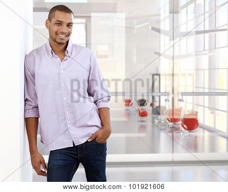 Portrait of casual black office worker leaning against wall. Happy, smiling, copyspace, looking at camera.
