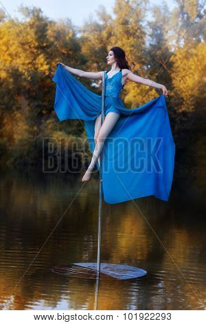 Girl In A Blue Dress Sits High On Pole Dance.