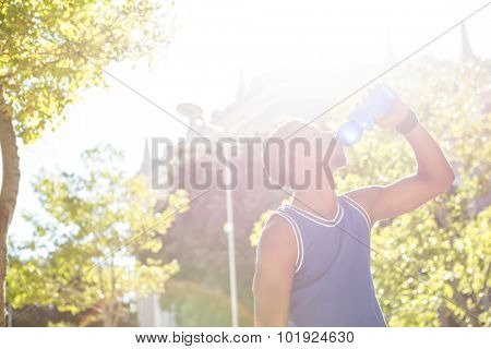 An handsome athlete drinking water on a sunny day