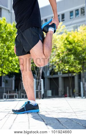 Low angle view of an athletic man doing a leg stretching
