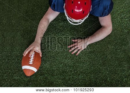 Upward view of an american football player scoring a touchdown