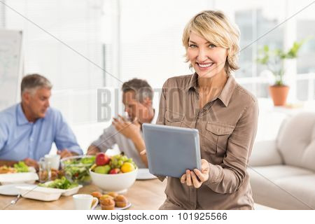 Portrait of smiling casual businesswoman using tablet at lunch in the office