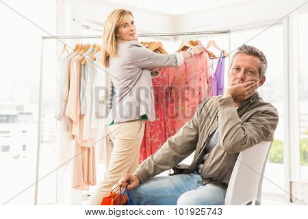 Portrait of bored man waiting for his shopping woman in clothing store