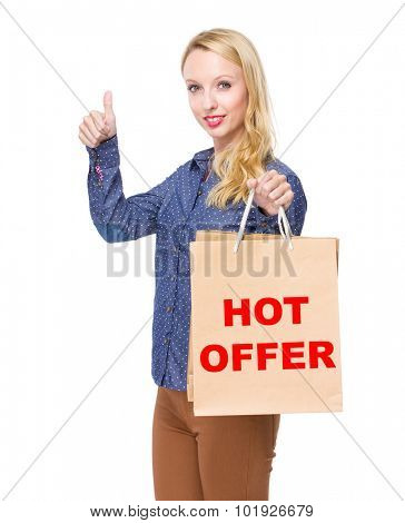 Woman with shopping bag and thumb up for showing phrase of hot offer
