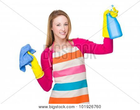 Housewife cleaning with rag and bottle spray