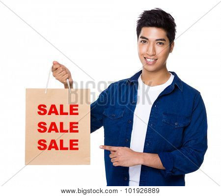 Man finger point to shopping bag for showing three sale words