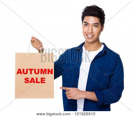 Man finger point to shopping bag for showing phrase of autumn sale