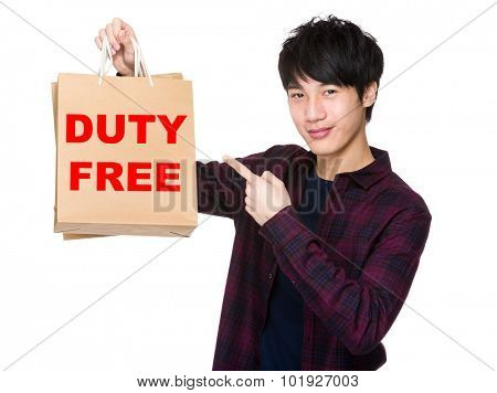 Happy young shopper with finger point to paper bag for showing phrase of duty free