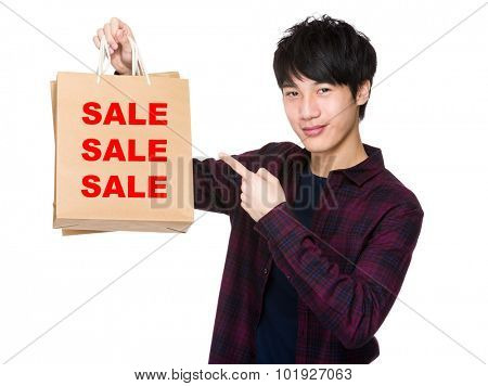 Happy young shopper with finger point to paper bag for showing three sale words