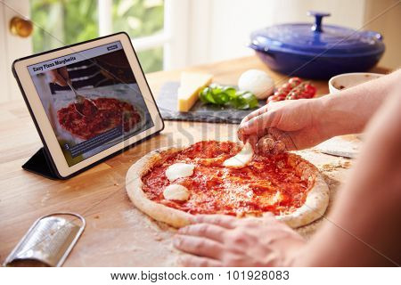 Person Following Pizza Recipe Using App On Digital Tablet