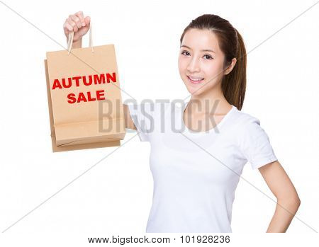 Woman hold with shopping bag and showing phrase of autumn sale