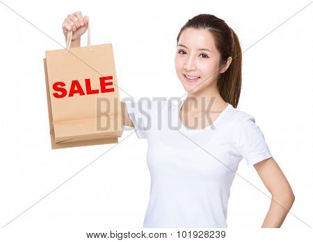 Woman hold with shopping bag and showing a word of sale