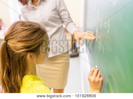 education, elementary school, learning, math and people concept - close up of little schoolgirl with teacher writing on chalk board and solving task at classroom