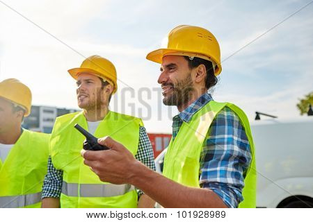 industry, building, technology and people concept - happy male builders in high visible vests with walkie talkie or radio outdoors