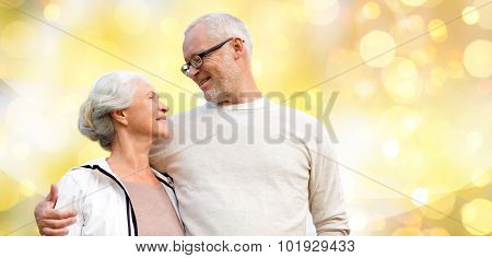 family, relations, age and people concept - happy senior couple over holiday lights background