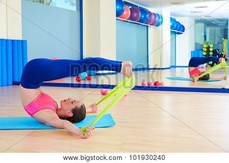 Pilates woman roll over rubber band exercise workout at gym indoor