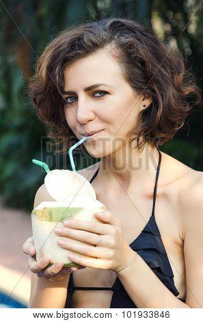 Woman in bikini drinks fresh coconut with strobe