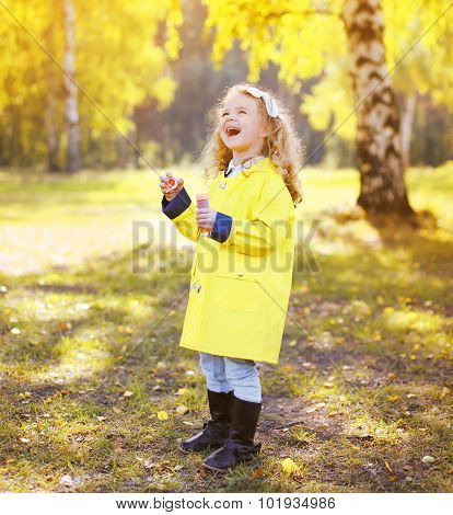 Laughing Little Girl Child Wearing Yellow Jacket In Sunny Warm Autumn Day