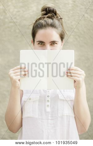 Woman Hiding Half Of Her Face Behind Empty White Paper Notebook