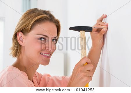 Young Woman Hitting Nail In A Wall