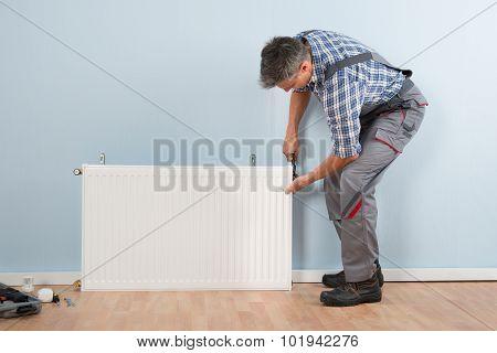 Male Plumber Fixing Radiator