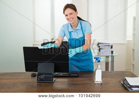 Woman In Workwear Rubbing Computer
