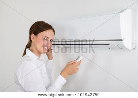 Businesswoman Operating Air Conditioner
