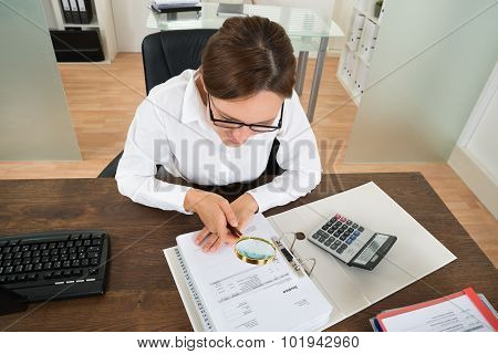 Businesswoman Looking At Invoice Through Magnifying Glass