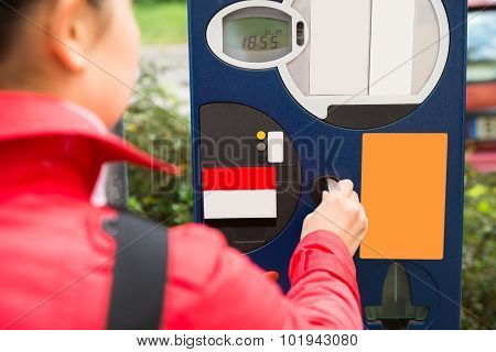 Woman Inserting Coin In Parking Meter