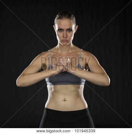 Intense Athletic Woman Holding Fist in Studio