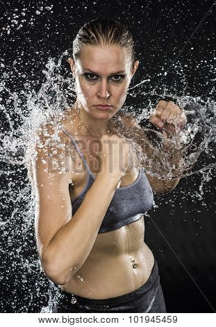 Athletic Woman in Combat Pose in Water Splashes