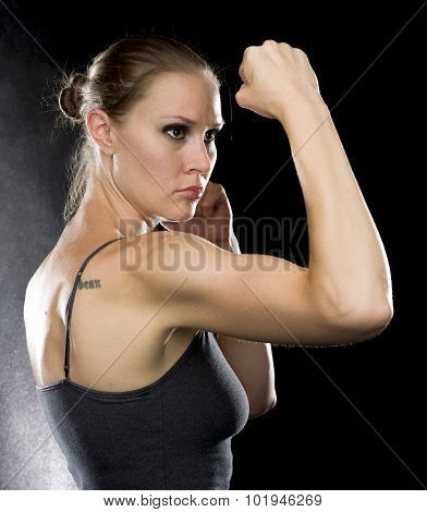Sporty Woman in Combat Pose Against Black