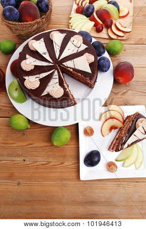 chocolate cream brownie cake layers slice topped with white chocolate and cream flowers decorated with fruits apple plum and grape on plate on wooden table with big whole cake