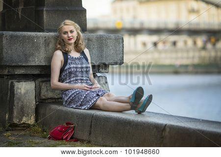 Young beautiful woman sitting relaxed on the promenade.