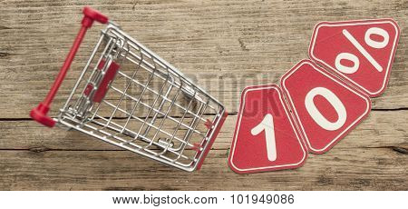 discount 10%, shopping cart on wood background