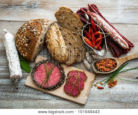 grey bread and different kind of salami isolated on wooden background