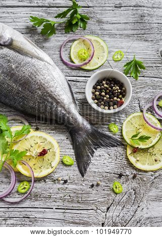Fresh Dorado Fish With Lemon, Spices And Herbs On A Light Wooden Surface