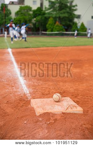 Baseball And Base On Baseball Field With Players Practising On Background