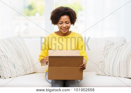 people, delivery, shipping and postal service concept - happy african american young woman opening cardboard box or parcel at home